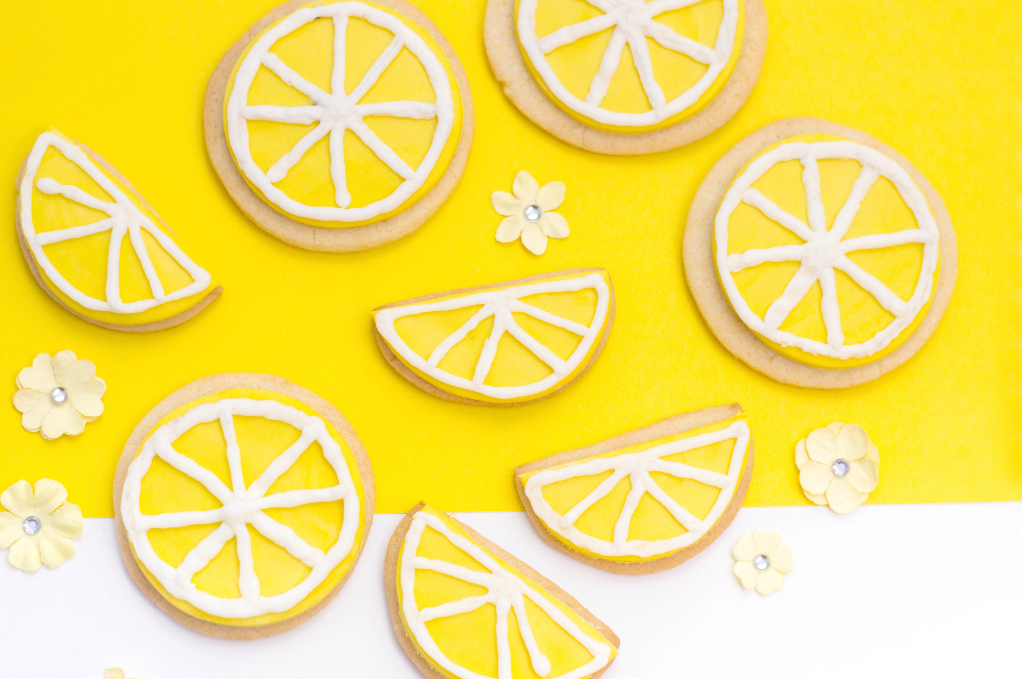 A yellow and white background with little yellow flowers, cookies and half cookie wedges placed on top. Iced and they look like lemon wedges and lemon slices ready to eat!