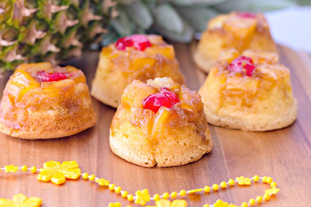 The finished product. Mini upside down pineapple cakes with a small lei and pineapple surrounding them.