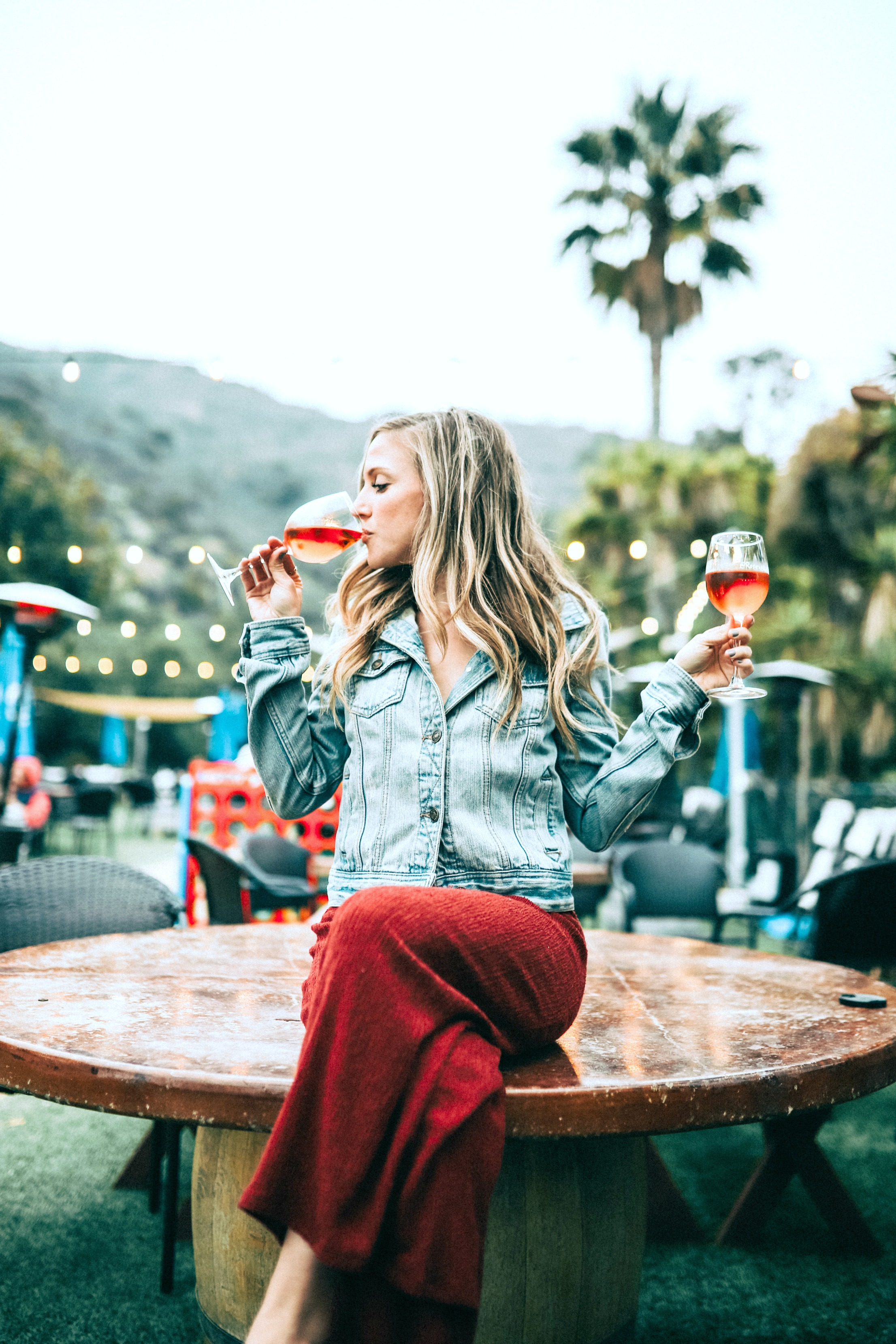 A woman sitting on a table drinking a glass of wine while she holds another glass of wine.