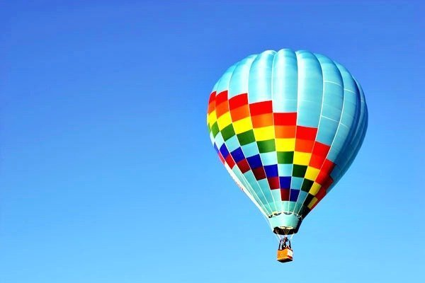 A hot air balloon ride is shown against a clear blue sky.