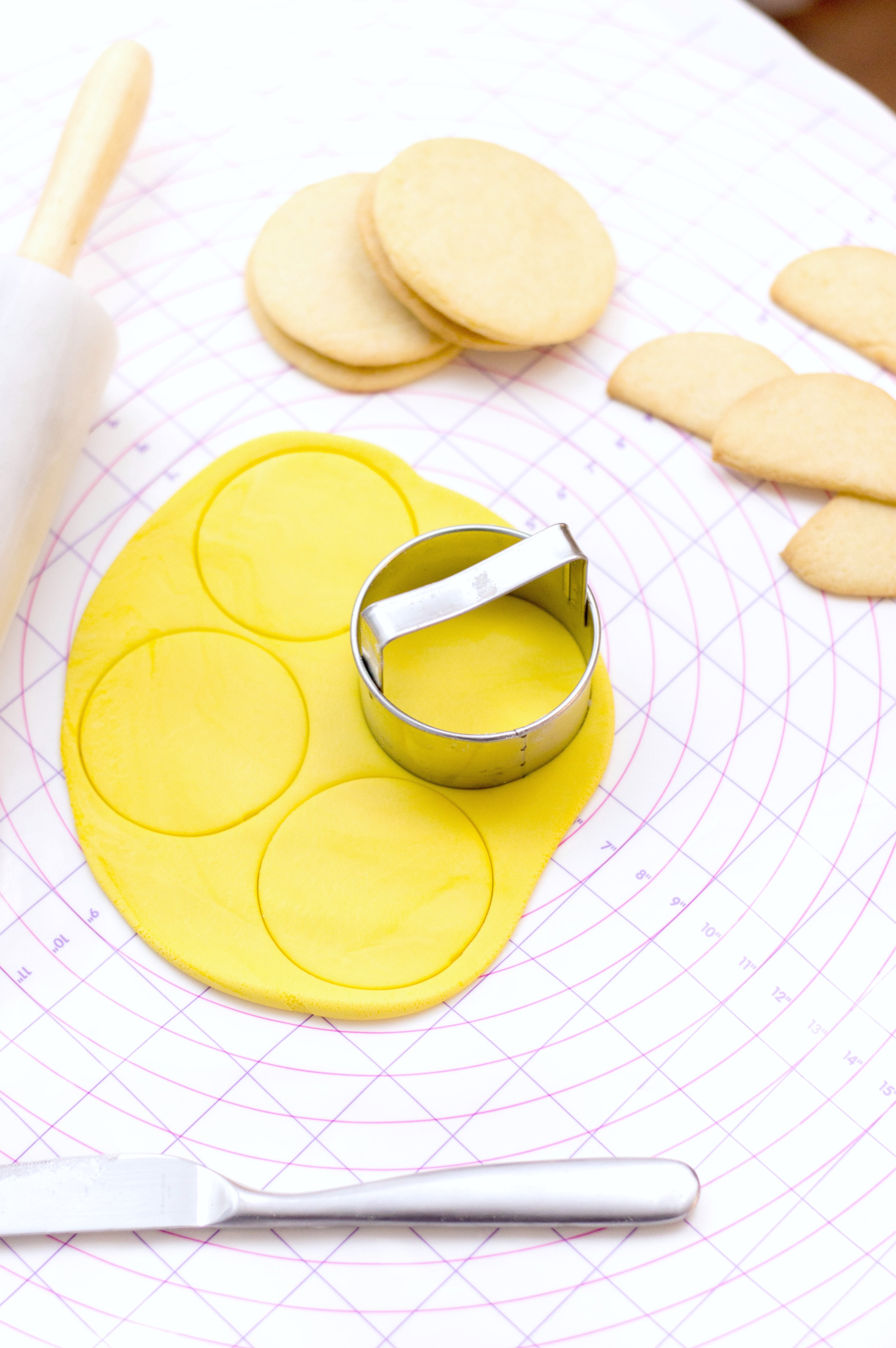 Yellow fondant is rolled out and cookies are piled up. Circles are being cut out with a cookie cutter to place on top of cookies.