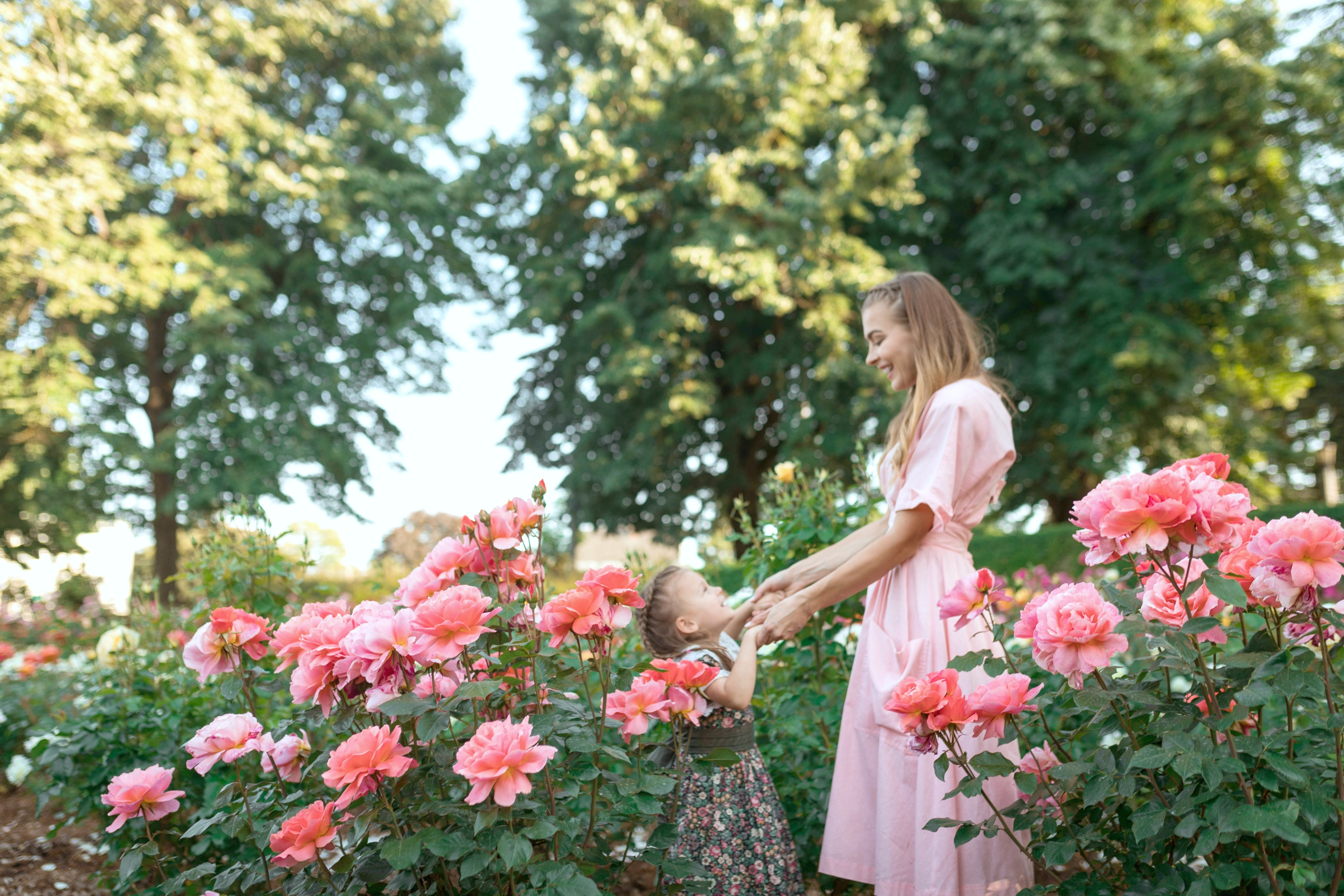 A young mom and her daughter hold hands inside rose bushes while they smile at each other.