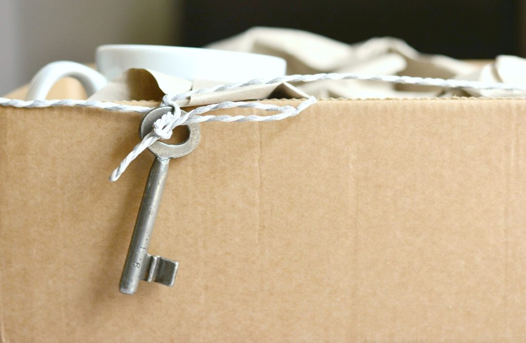 A box filled with mugs and a little key on a rope hangs off the mug and moving box.