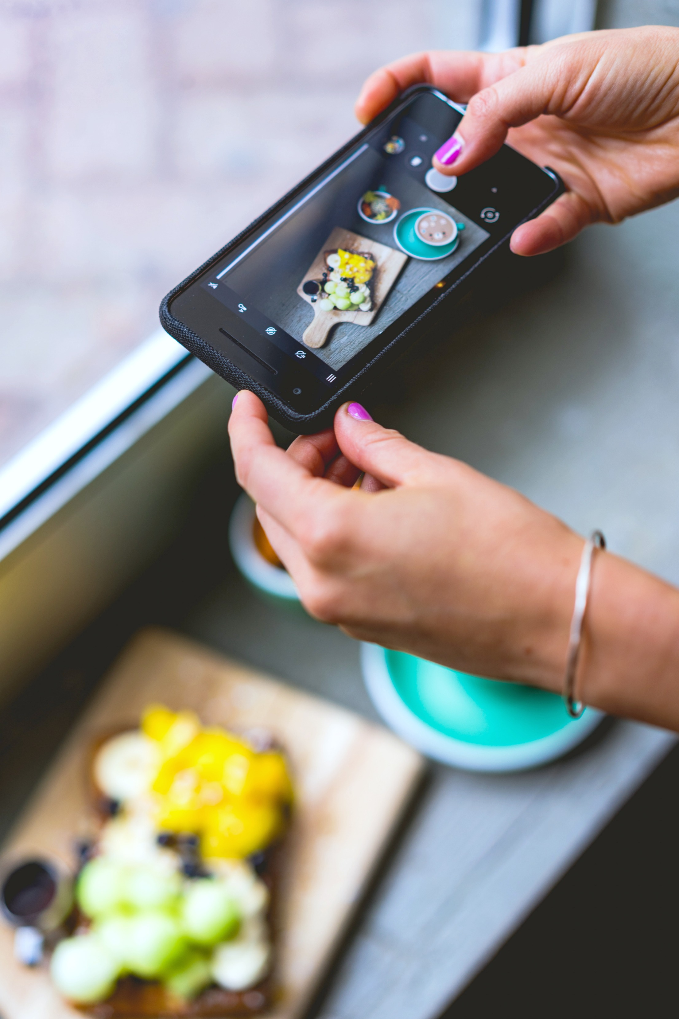A woman prepares a meal and photographs it with her smartphone.