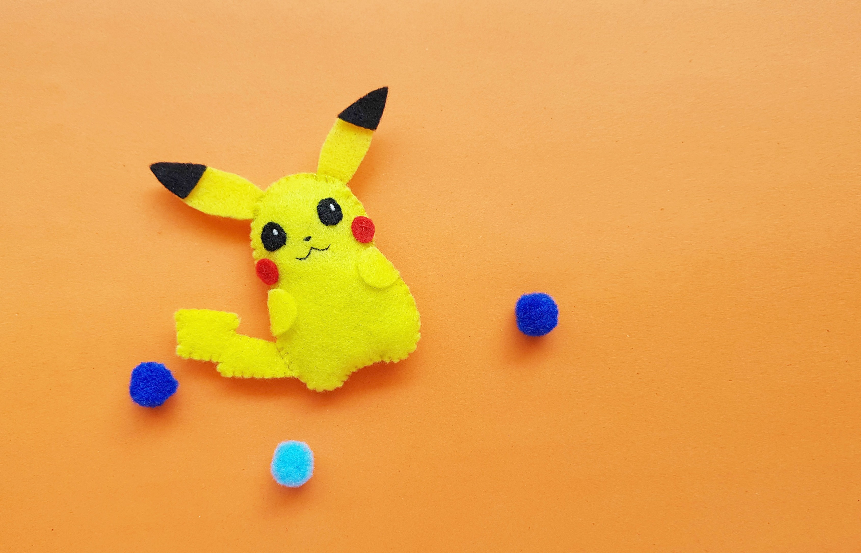 The finished product of Pikachu in all his glory against an orange background.