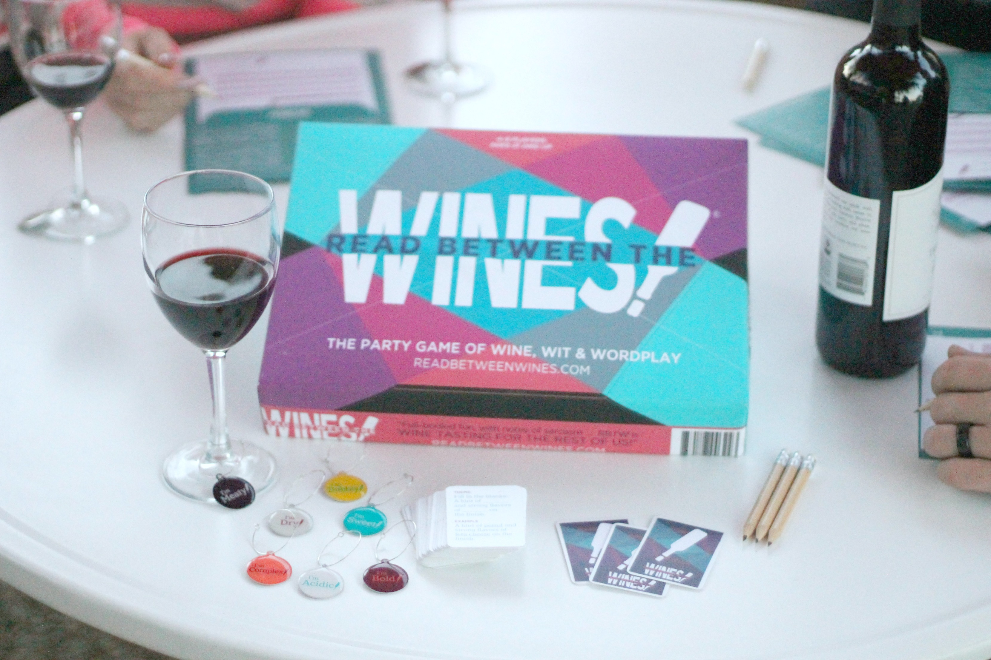A fun board game, Read Between the Wines is shown on a table with glasses of wine and ladies gathered to play the board game.