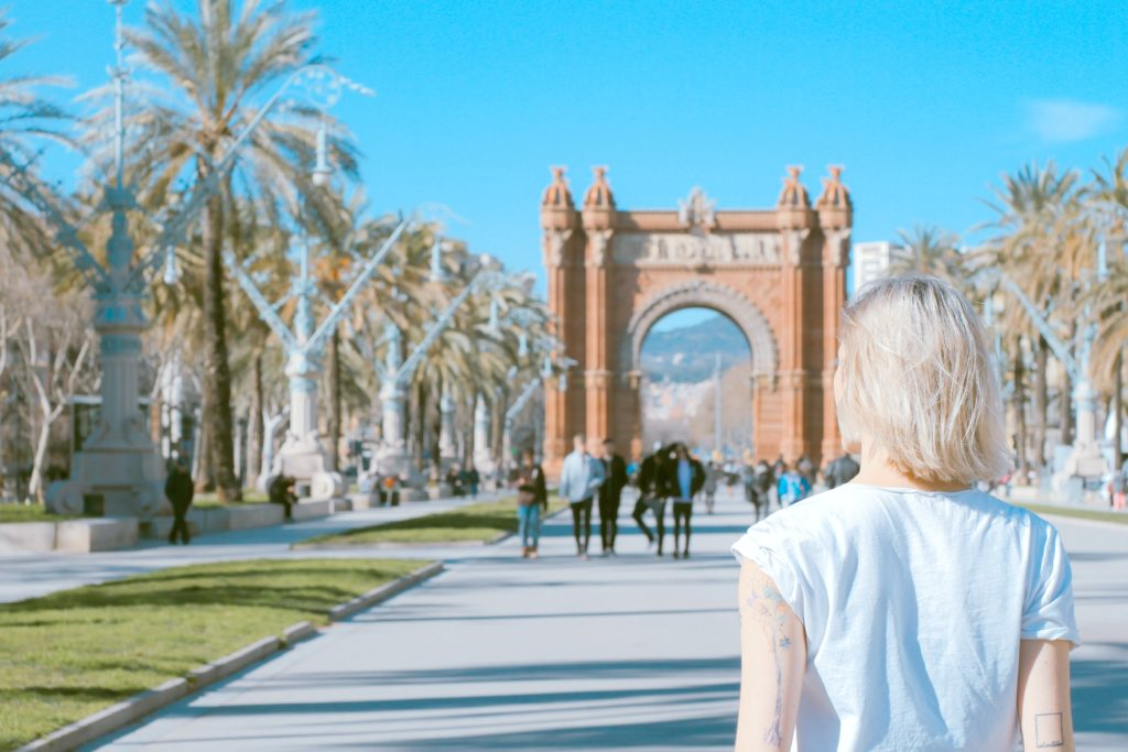A girl stands and people watches in Barcelona, Spain.