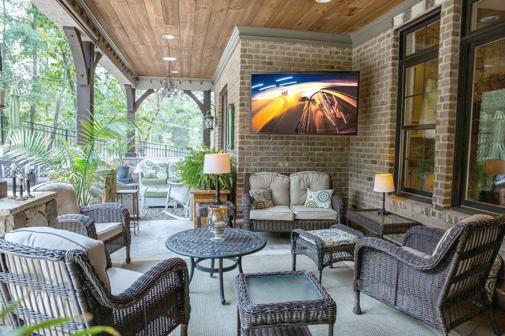 A beautiful outdoor space with comfortable furniture and a big screen TV.
