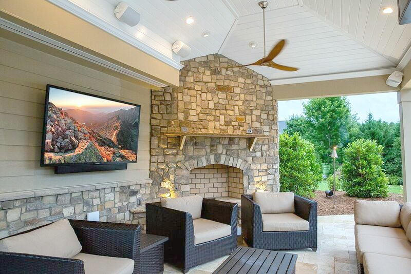 Outdoor space with a TV screen, furniture, fireplace, and fan.