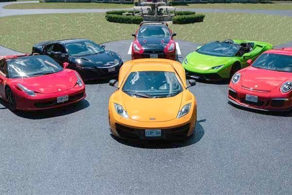 A group of exotic cars are parked facing the camera, as in an invitation to get in and ride.