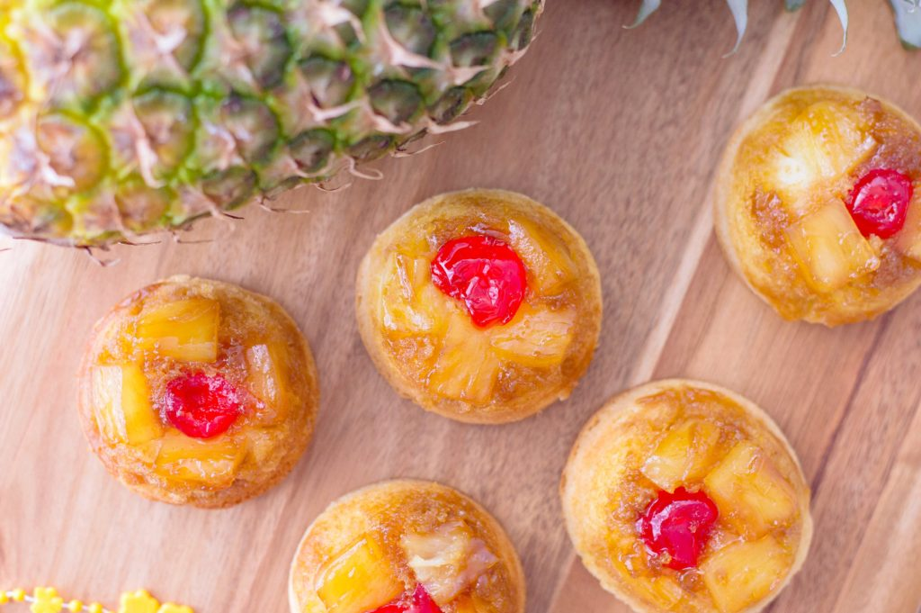 Top view of mini upside down pineapple cakes on a wood backdrop. Entire pineapple can be seen.