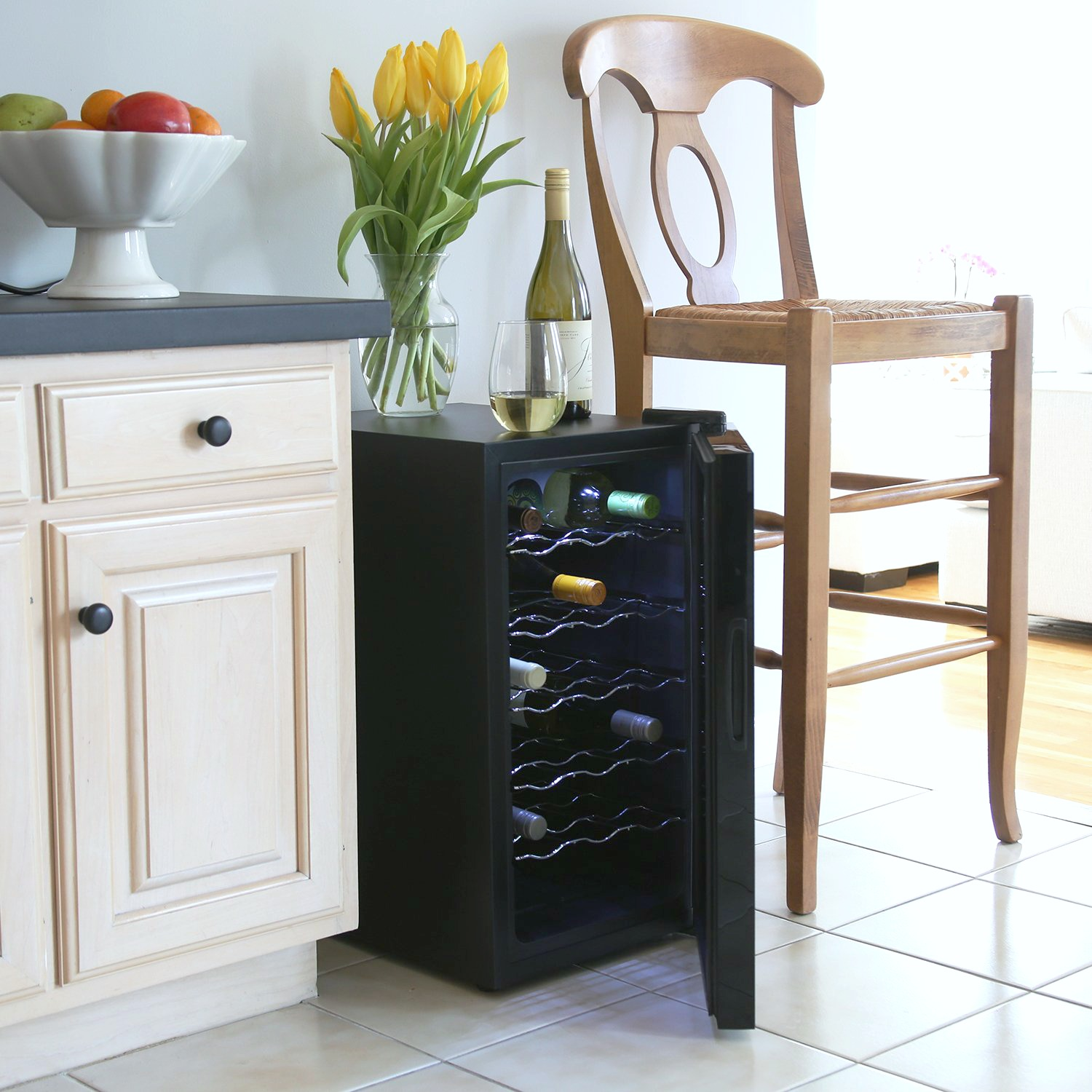 A small black wine cooler has its door ajar and next to a chair and kitchen cabinet.