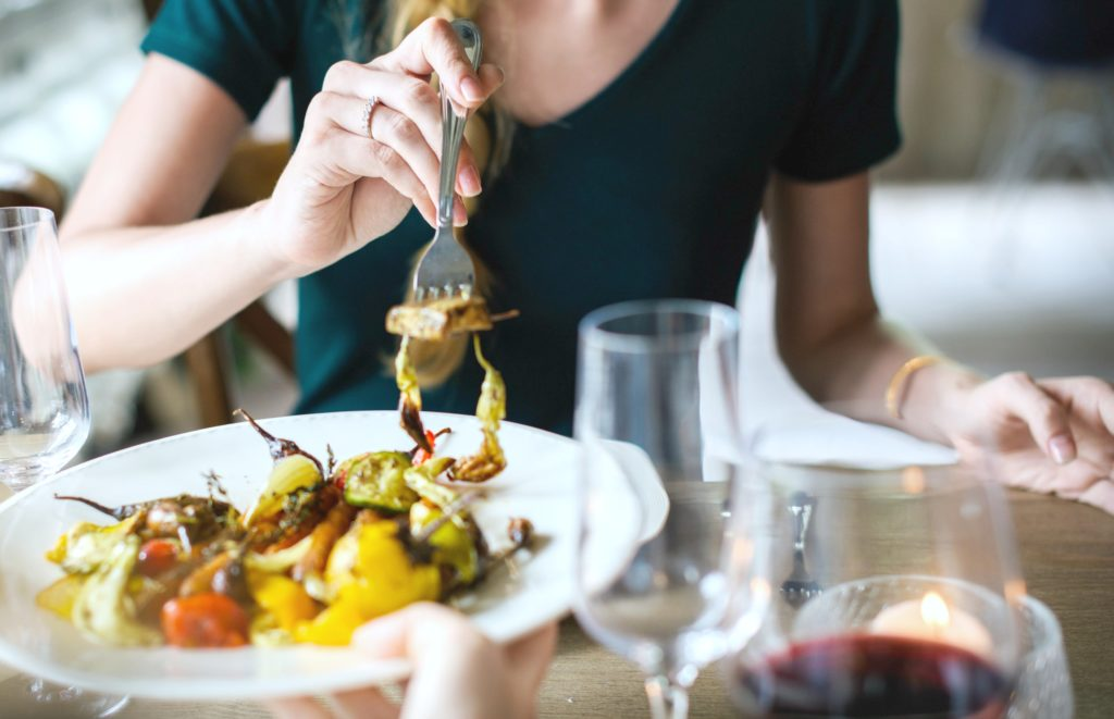 Woman dines out and shares plate with partner.