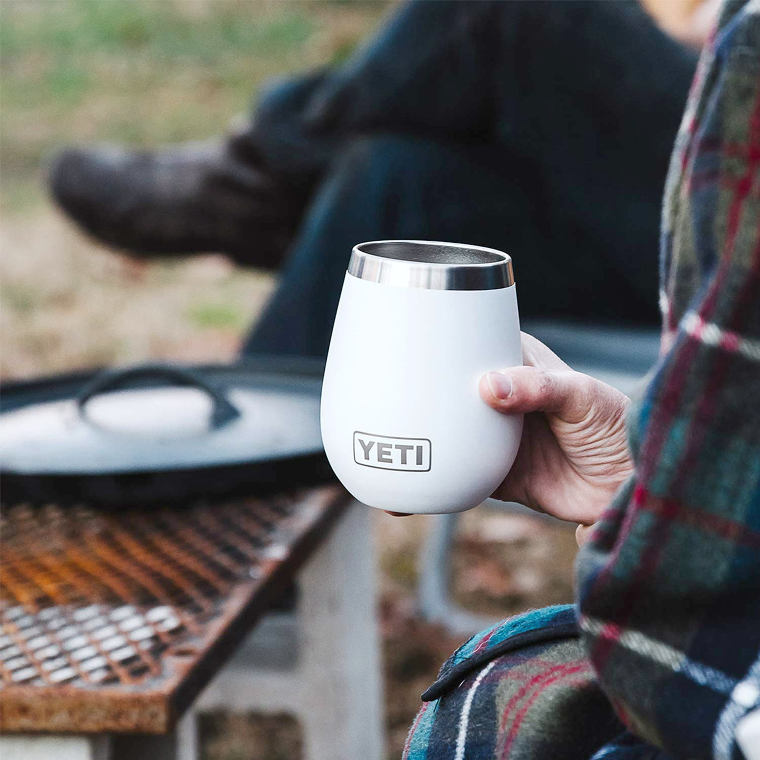 A woman holds a Yeti wine cup while wrapped a blanket around a fire.