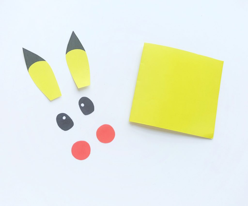 Eyes are coloured black with a yellow speck, ear tips are coloured in as well. The Pokemon Mini Notebook sits next to pieces.
