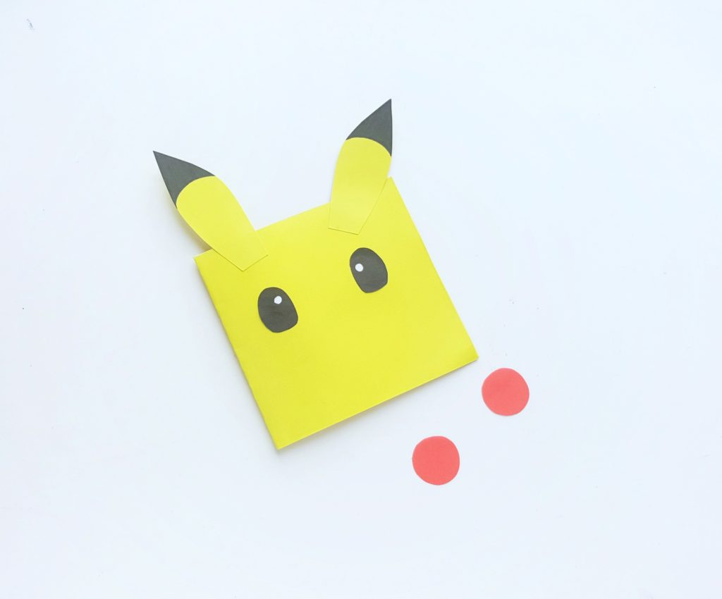 Ears glued onto the yellow Pokemon Mini Notebook, eyes glued on, and cheeks about to be glued on.