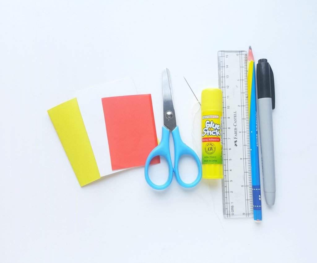 Supplies Needed to Make Pokémon Notebooks: coloured paper, scissors, needle and thread, glue stick, ruler, pencil, and marker.