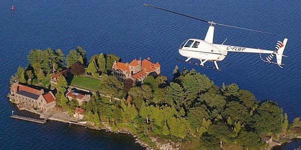 A white helicopter flies over the 1000 islands in Vancouver. Totally the best experiences to give dad.