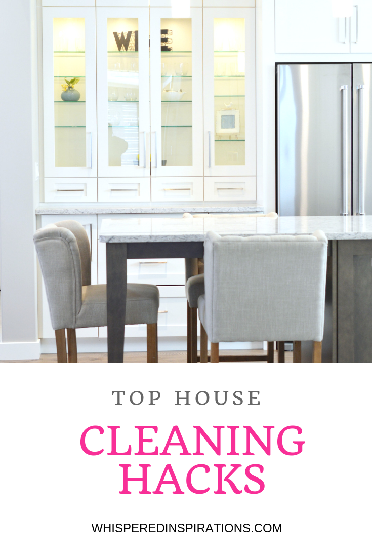 A beautiful white kitchen is shown, two chairs, an island, a stainless steel fridge and it's clean due to the top house cleaning hacks.