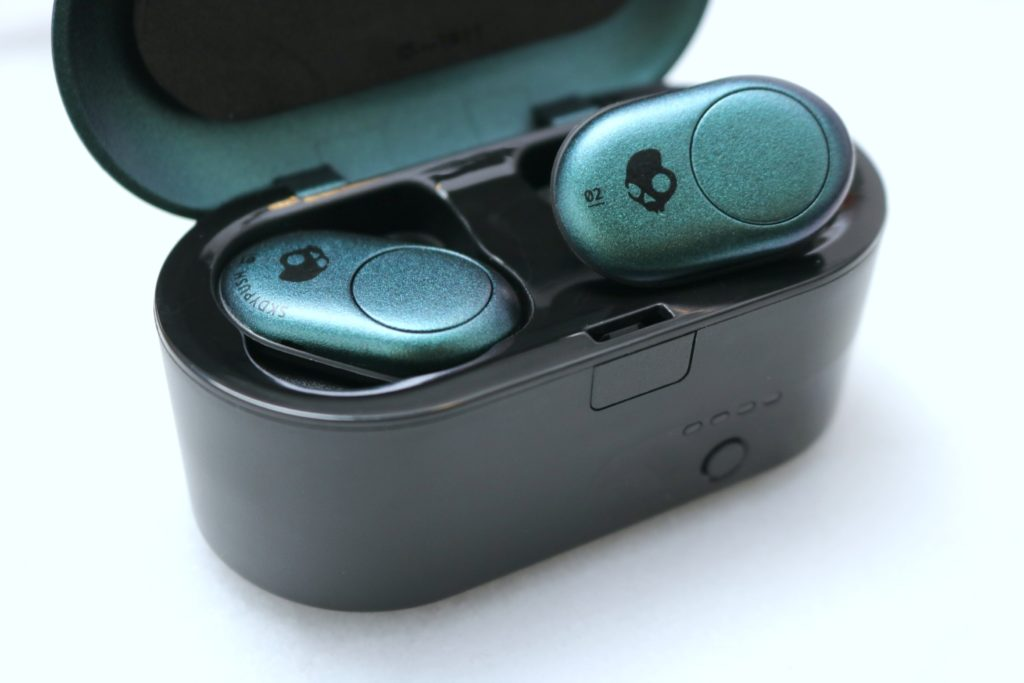 A charging case with the Skullcandy Push earbuds, one is plugged in, the other is showing the camera.
