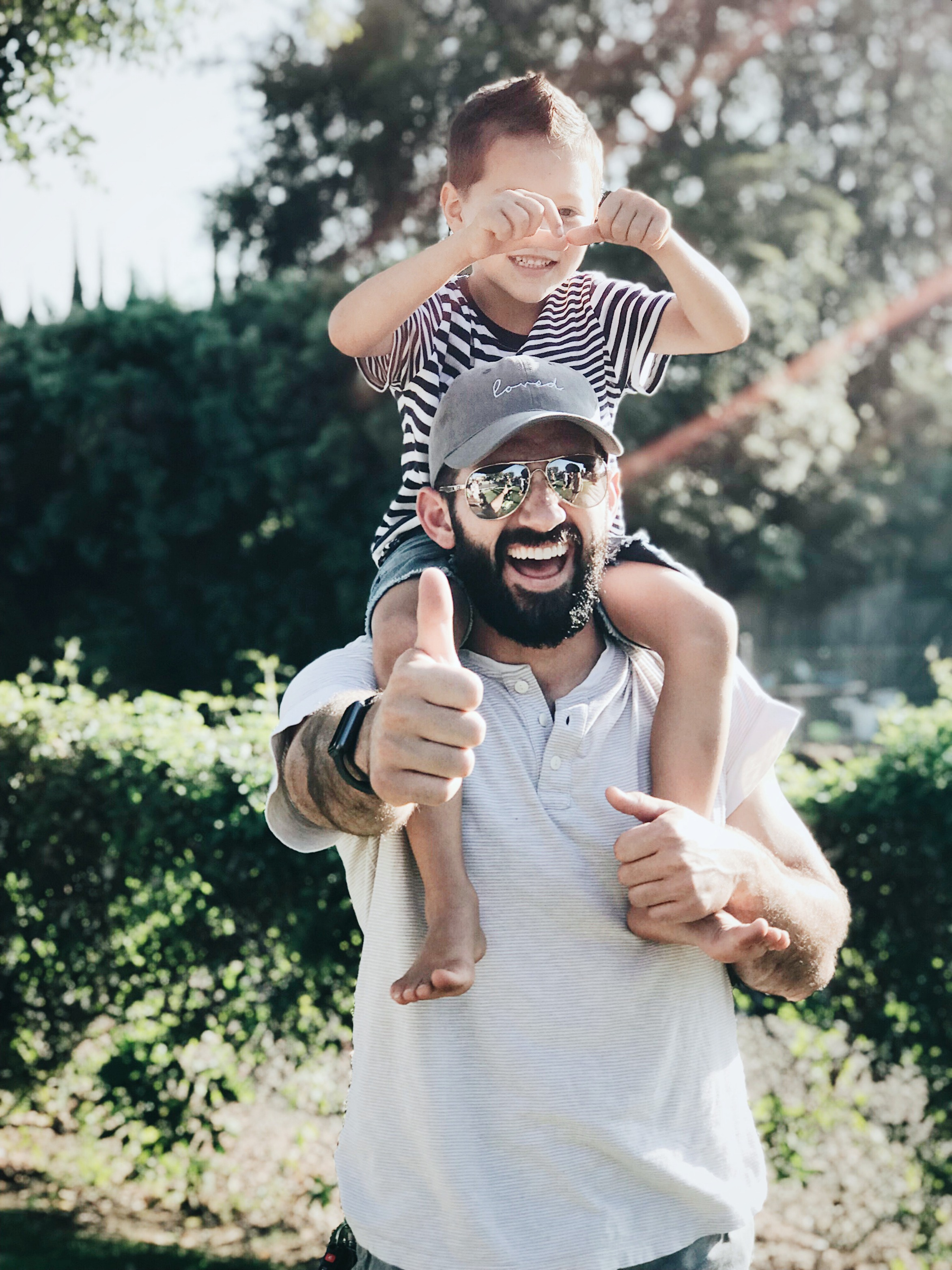 A dad wearing sunglasses holds his son on his shoulders, he smiles and gives the camera a thumbs up. Following is a list of the best experiences to give Dad.
