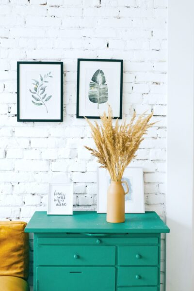 A painted white brick wall, with a teal nightstand with two pictures on the wall and flowers on the table.