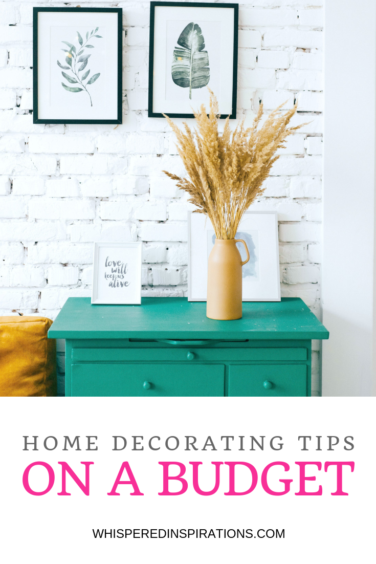 "A painted white brick wall, with a teal nightstand with two pictures on the wall and flowers on the table. An easy way to decorate on a budget. Underneath is a banner that reads, ""Home Decorating Tips on a Budget"""