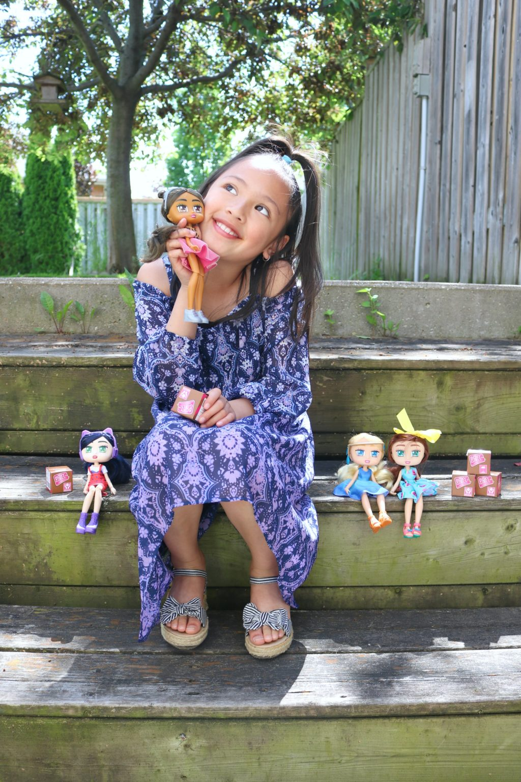 Mimi, a little girl, tilts her head and holds a Boxy Girl next to her cheek and smiles.