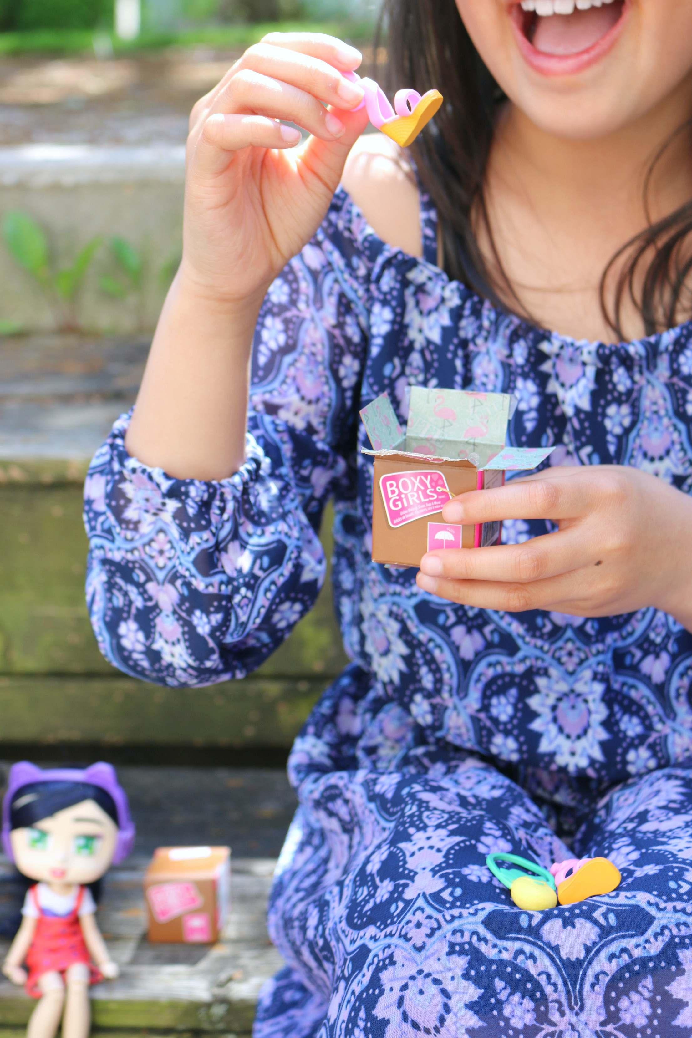 A close up of a little girl unboxing a mini Boxy Girl box, she pulls out a shoe. In the background is a Boxy Girl with another surprise box.