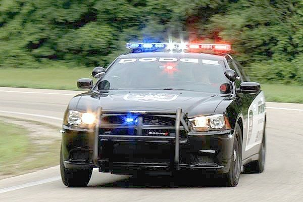 A Dodge Charger police squad car is racing down a track with all their lights on.