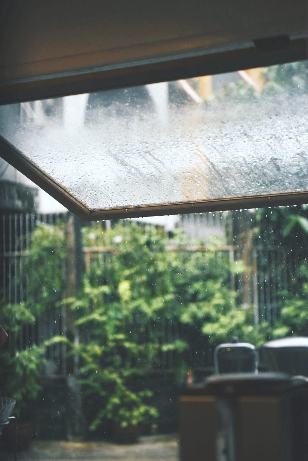 A backyard porch shows rain falling and makes you think of ways to prepare for storm season.