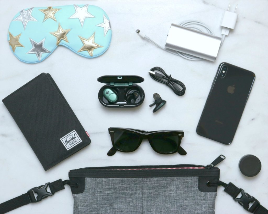 A flat lay picture of a personal messenger bag with the inside components spread out: a passport holder/wallet, sunglasses, Skullcandy Ear Buds, phone, chargers, lip balm, and a sleeping mask.