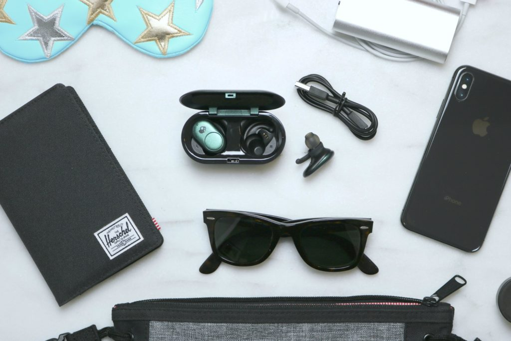 A close up of a flat lay picture of a personal messenger bag with the inside components spread out: a passport holder/wallet, sunglasses, SkullCandy Ear Buds, phone, chargers, lip balm, and a sleeping mask.