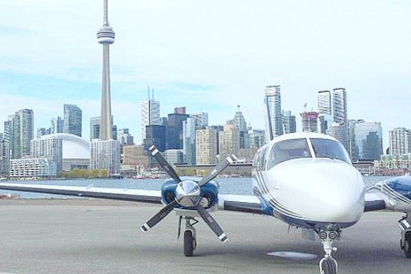 A propeller plane is seen at the airport, behind it is the CN tower. It truly is one of the best experiences to give dad.