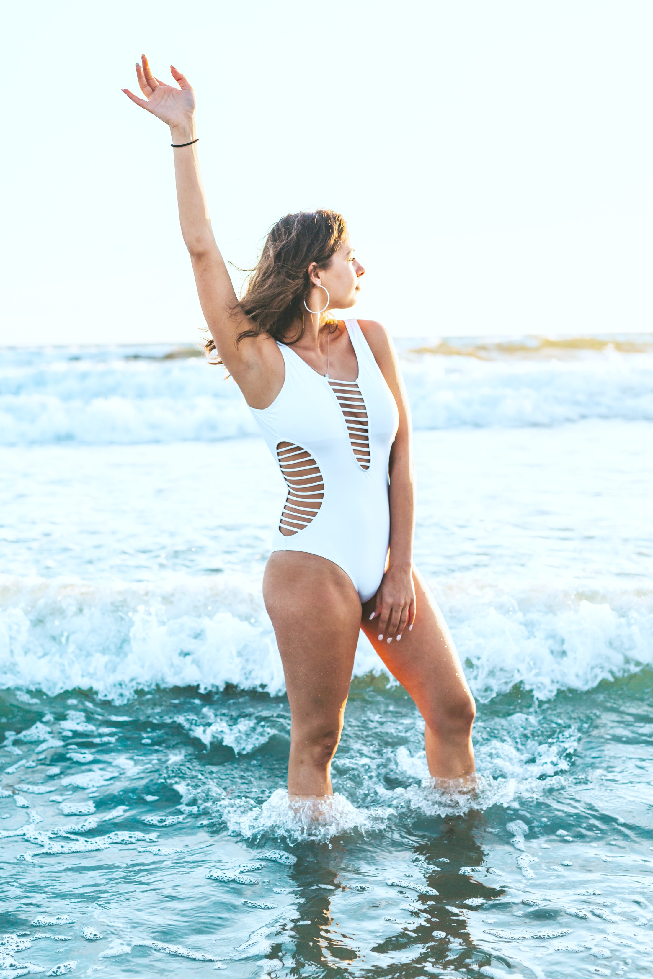 Confident woman in a one piece bathing suit in the ocean, throwing her hand in the air and looking towards the horizon.