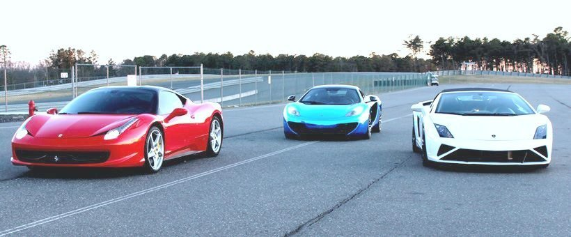 A Lamborghini, and two Ferraris are shown on a race track, waiting to be driven.