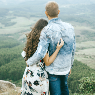 A young couple poses in front of a hillside facing towards the edge.