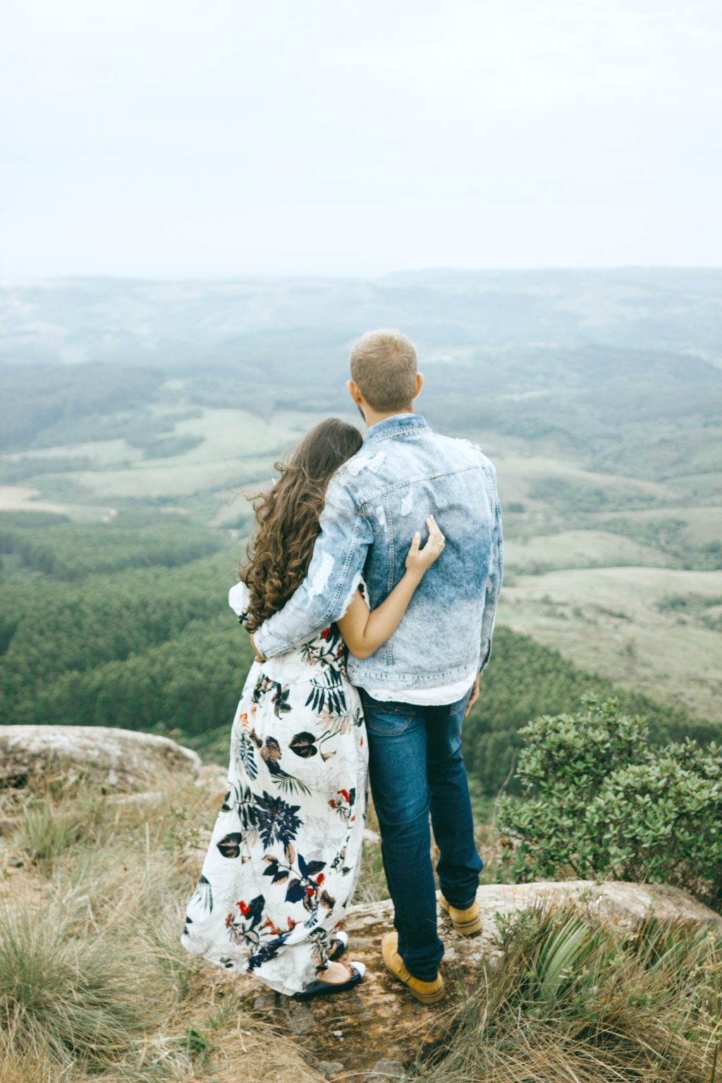 A couple looks over a hill together, only their backs are seen.