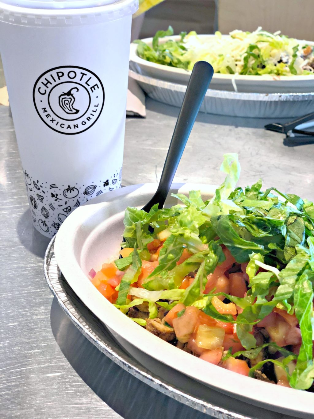 Chicken Bowl at Chipotle Mexican Grill, drink and another bowl is shown.