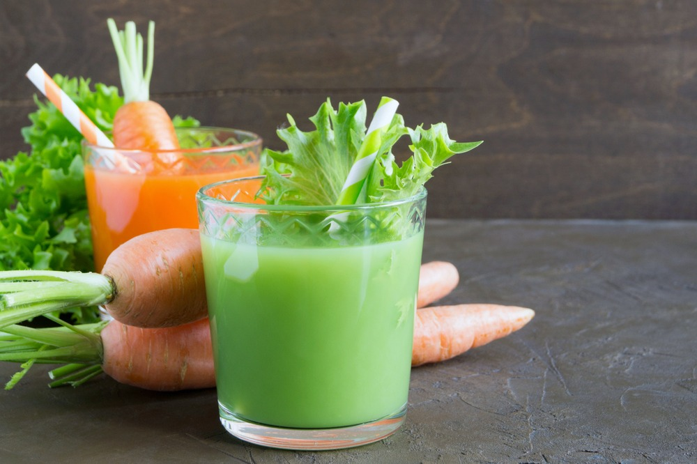 A cup of green juice, carrot juice, surrounded my fresh veggies.