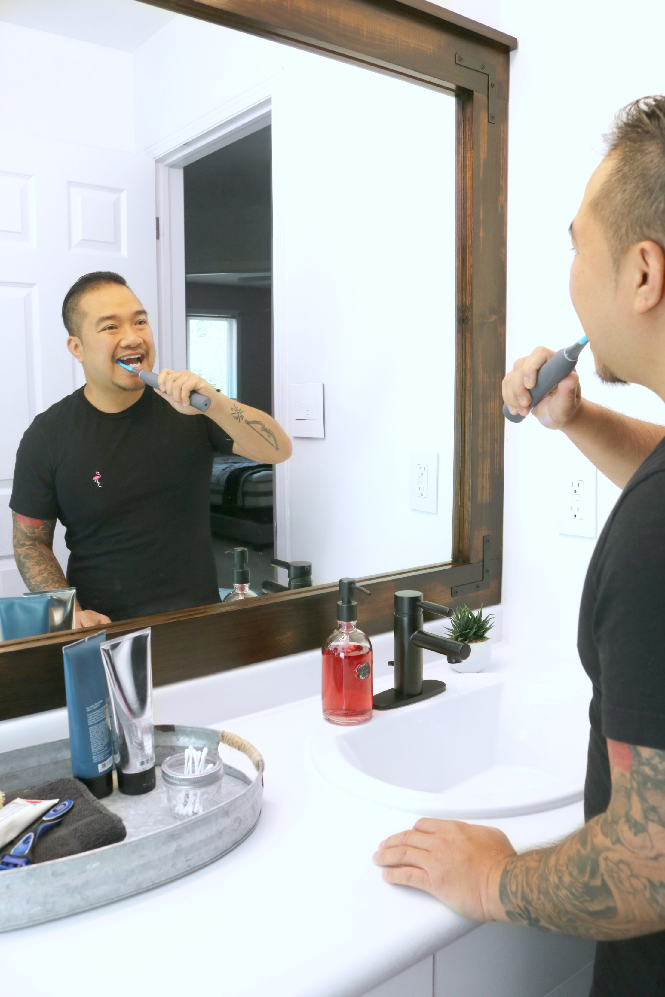 Darasak brushing his teeth in front of mirror with his Cari Pro toothbrush.