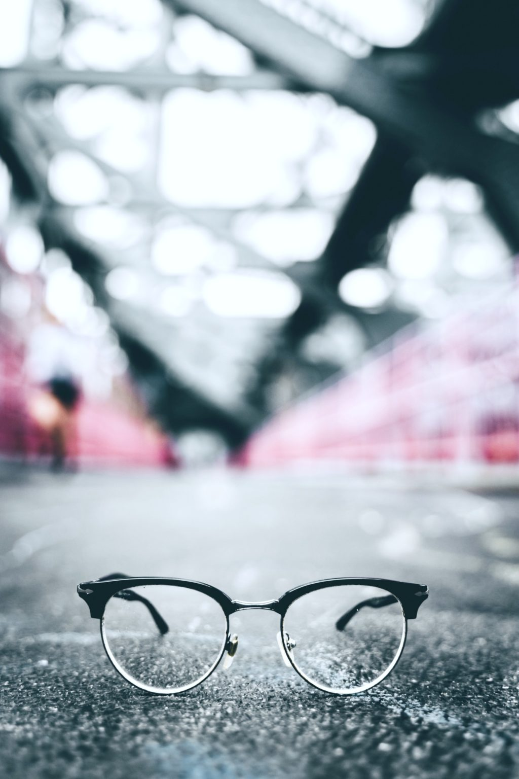 An artistic picture of Wayfarer glasses in an urban setting. They are on the concrete and looks like a blurred subway station in the back.