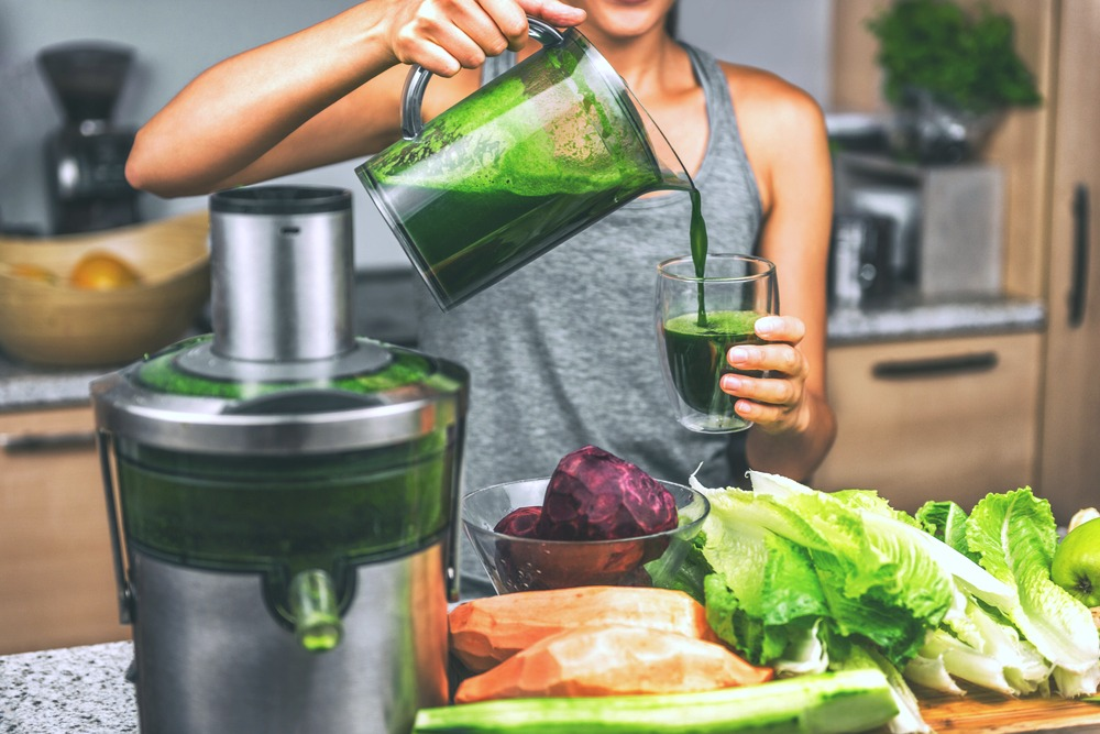 A woman juices veggies and makes green juice, she pours it into a cup.