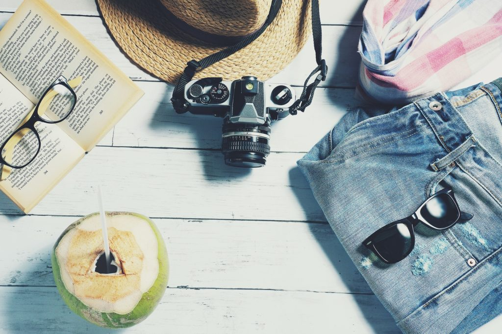 A hat, camera, book with eyeglasses, jeans, a shirt and a coconut drink are shown in flat lay.