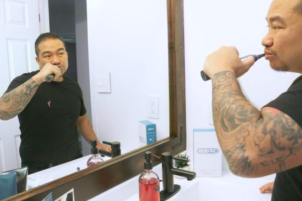 Darasak is brushing his teeth with his cariPRO.