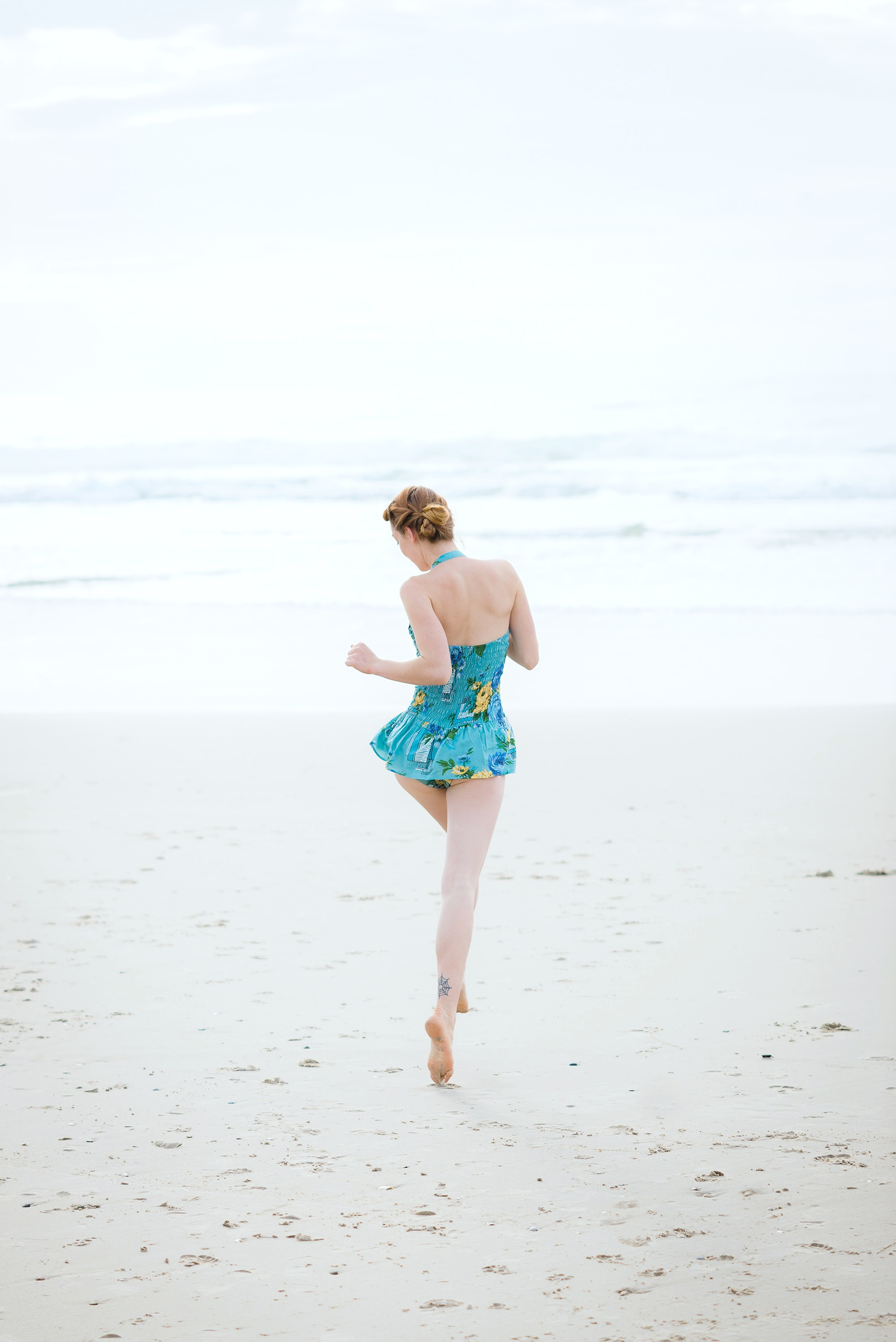Woman prancing on the beach in a blue bathing suit.