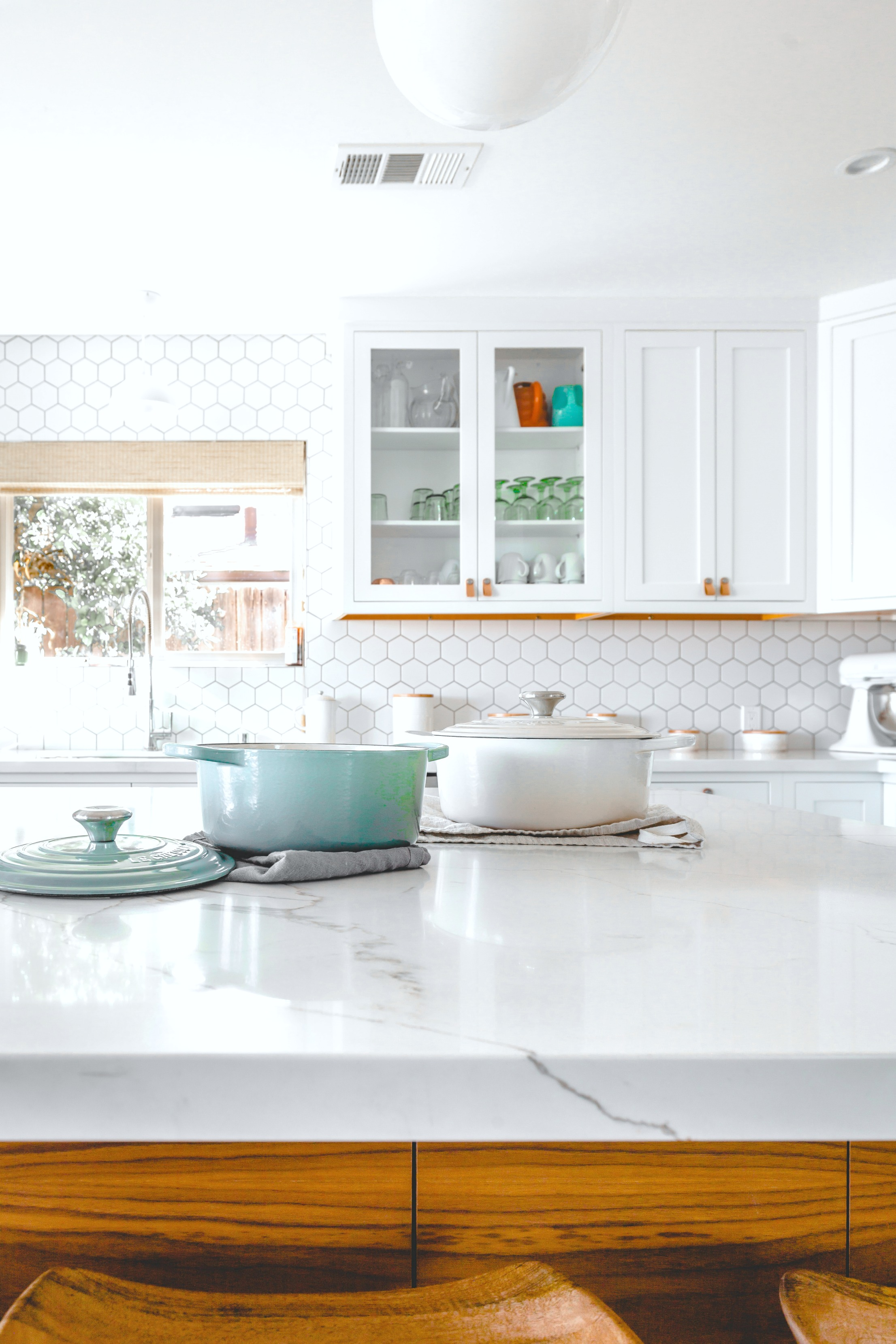 A close up of cooking pots to be used for cooking in a beautiful white kitchen with many appliances.