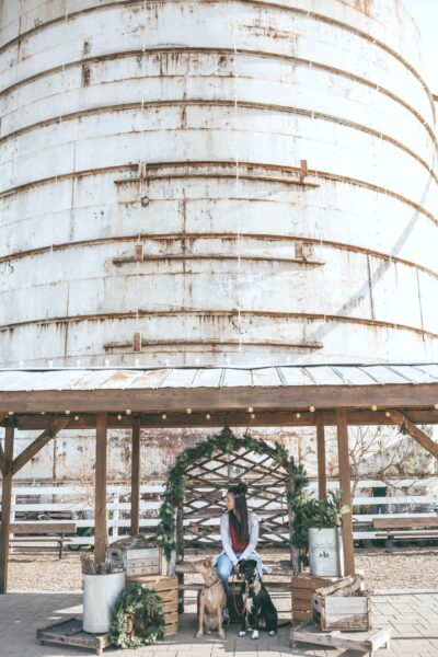 A silo is behind a woman selling wreaths and other greenery. Steel buildings on a rural property.