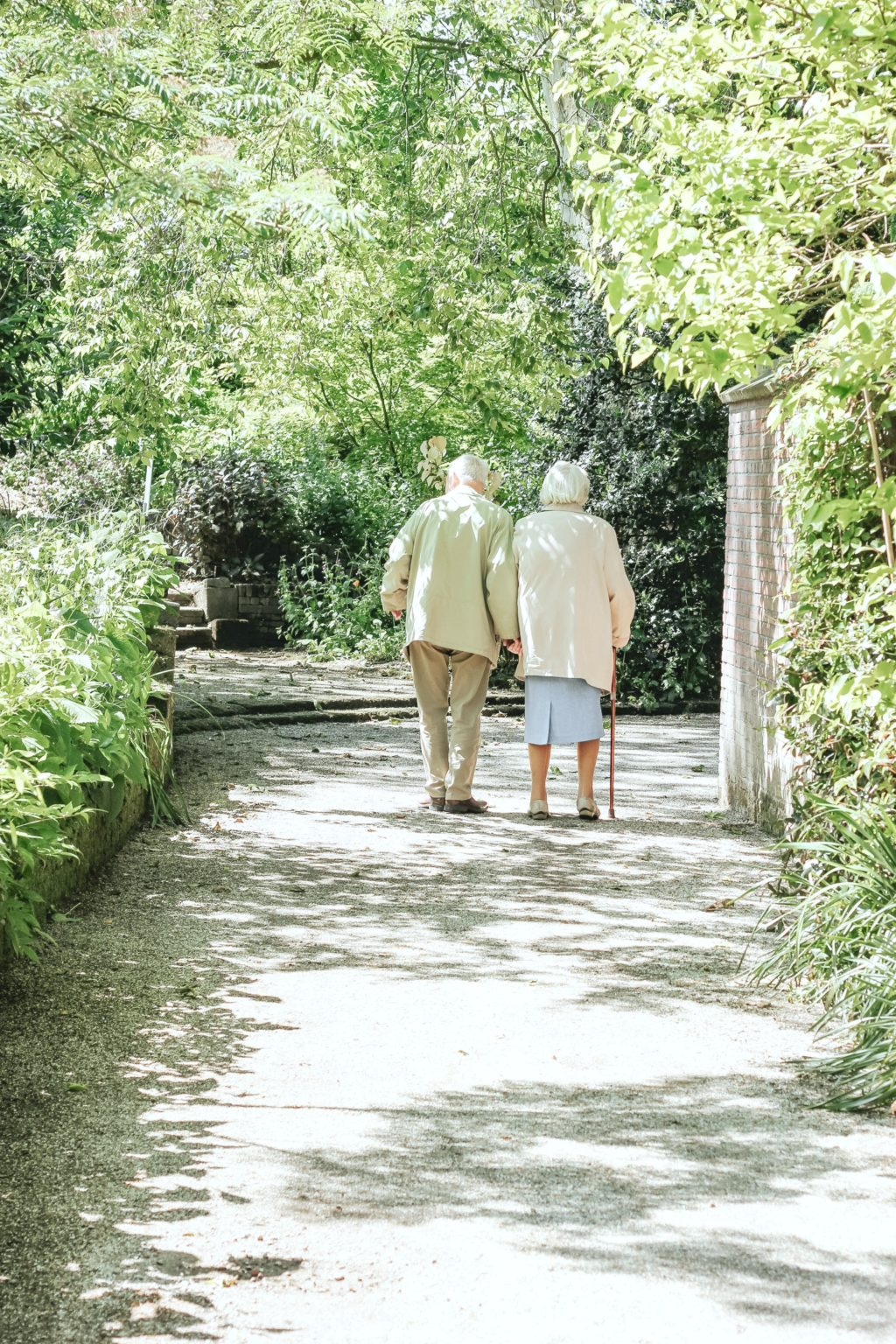 Two elderly people walk along a forested path