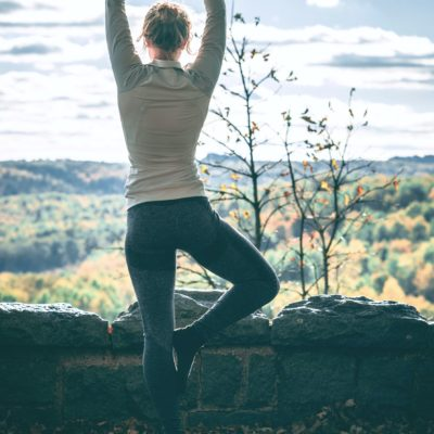 Woman stands at a hillside and does yoga, she strikes a pose.